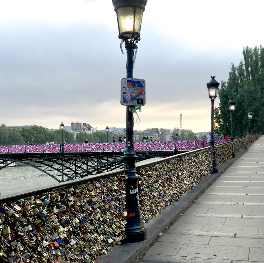 "Only the ""love locks"" lining the walk up to the Pont des Arts remain. The walls of the bridge crossing the river have been removed and replaced by paintings by Parisian graffiti artists."